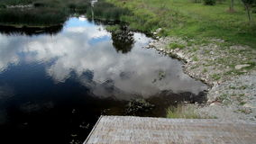 Tranquil scenery of pond near the cabin and wooden shingle roof stock video