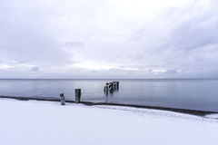 Tranquil sea with broken pier posts leading into the water, snow Stock Photos