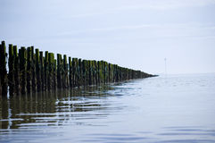 Tranquil sea perspective. Sea defences at Mersey beach, Suffolk, UK stock images