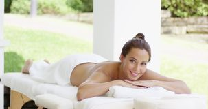 Tranquil spa customer relaxes on table. With chin on folded towel in outdoor patio stock video footage