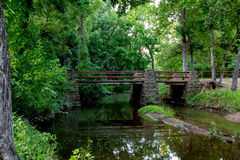 A Tranquil Spring or Summer Wooded Nature Outdoor Scene. With bridge over creek or river Stock Image