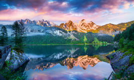 Tranquil summer scene on the Vorderer Gosausee lake in the Austr. Ian Alps. Colorful sky reflected from mirror surface of lake. Austria, Europe Stock Photos