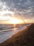 Tranquil sun setting on horizon over ocean with fishing rod in foreground Stock Image
