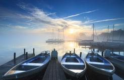 Tranquil sunrise at marina. Foggy and tranquil sunrise at some boats in a small marina on a lake Stock Images