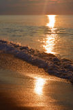 Tranquil Sunrise Over Ocean with Golden Waves. The sunrises over the ocean on a summer morning Stock Photography