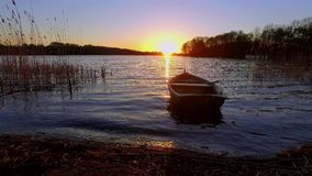 Tranquil sunset with the lake and boat stock video footage