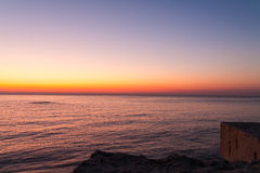 Tranquil sunset over ocean horizon. Tranquil vivid orange and purple sunset over calm ocean horizon with rocks and balcony in foreground Stock Photos