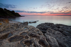 Tranquil sunset on the rugged coastline. Beautiful sunset over the tranquil waters of the Severn Estuary looking across to South Wales from Portishead in stock images