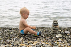 Tranquil toddler meditating on the sea beach. Cute baby boy relaxing and looking to the stone pyramid. Tranquil toddler meditating on the sea beach. Cute baby Royalty Free Stock Photography