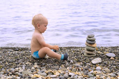 Tranquil toddler meditating on the sea beach. Cute baby boy relaxing and looking to the stone pyramid.  Royalty Free Stock Photography