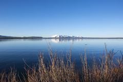 A tranquil view of snow capped mountains over a lake. A tranquil view of snow capped mountains reflecting on a calm, glassy lake under clear blue skies, nestled royalty free stock photography