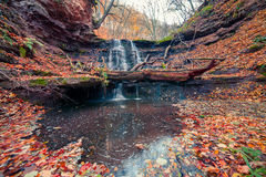 Tranquil waterfall scenery in middle of autumn forest. Stock Photo