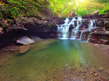 Tranquil waterfall scenery in middle of green forest Royalty Free Stock Photography