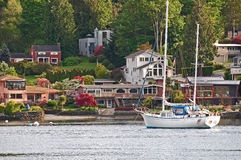 Tranquil waterfront neighborhood. A sailboat rests by a tranquil waterfront neighborhood along Seattle's ship canal Royalty Free Stock Photo