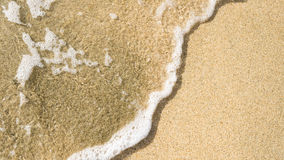 Tranquil wave washes over beach sand Royalty Free Stock Images