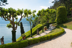 Tranquil winding path along the shore of lake Como. Tranquil winding path in the Villa Balbianello garden along the shore of lake Como, Italy royalty free stock image