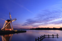 Tranquil windmill. Traditional windmill at a lake just after a tranquil sunset. Long exposure royalty free stock image