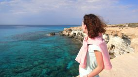 Tranquil woman enjoy rocky sea landscape. Tourist woman relaxing on sea shore. At summer vacation. Thoughtful woman on rocky cliff at holiday trip. Alone woman stock video footage