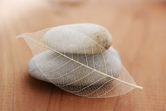 Tranquility. Stacked stones and skeleton leaf on warm wood background stock photos