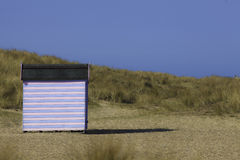Tranquility at the Beach. Solitary blue and pink striped wooden beach hut on the English coast. Many possible connotations relating to vacation, isolation and Royalty Free Stock Photo