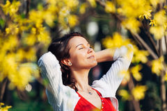 Tranquility. Carefree smiling woman behind leafs with arms holding her hair looking at the sun Stock Photography