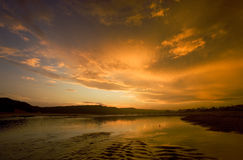 Tranquility in gold. Sunset over a river mouth with lovely cloudscapes Stock Photos