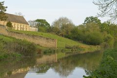 Tranquility. The Oxford canal runs by the old tithe barn at Upper Heyford, Oxfordshire Stock Images
