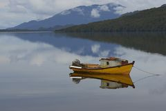 Tranquility of Patagonia at Puyuhuapi, Chile. Small boat moored on the still waters of a sea loch at Puyuhuapi, a small town on the Carretera Austral in northern Stock Images