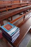 Tranquility place, Thai Catholic Prayer Book are on the rows of wooden church benches, soft beaming light shines in the church. Interior. Ancient church in stock photography