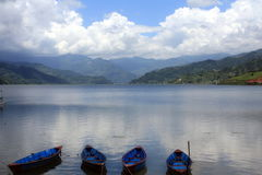 Tranquility on Pokhara Lake. Boats floating on the water Stock Image
