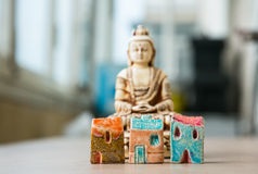 Tranquility and relaxation in megapolis. Three symbolic  toy ceramic houses in front of the Buddha statue Stock Images