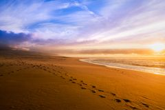 Beautiful sunset on a beach with footprints on the sand royalty free stock photo