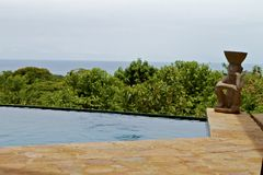 Tranquility. Stone-patio with private dipping pool overlooking tropical trees and the ocean Stock Photography