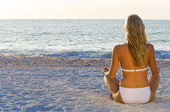 Tranquility Tides. A beautiful young blond woman wearing a white bikini sitting cross legged on a beach at sundown Stock Images
