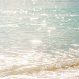 Tranquility time, beautiful surface of seawater in the morning, bright glittering star bokeh, soft waves and bubble. Tropical sea. In summer stock images