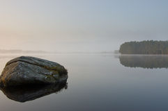 Tranquill lake in early morning mist Stock Photo