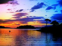Tranquillity and peace background at a power-full color-full sunset with canoe Stock Photo