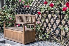 Tranquilo relaxe arbustos vermelhos do jardim banco romântico e cor-de-rosa cercados da flor das rosas Foto de Stock
