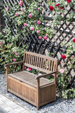Tranquilo relaxe arbustos vermelhos do jardim banco romântico e cor-de-rosa cercados da flor das rosas Fotografia de Stock