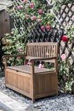 Tranquilo relaxe arbustos vermelhos do jardim banco romântico e cor-de-rosa cercados da flor das rosas Fotos de Stock Royalty Free