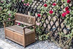 Tranquilo relaxe arbustos vermelhos do jardim banco romântico e cor-de-rosa cercados da flor das rosas Imagens de Stock Royalty Free