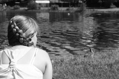 Tranquility. A young girl sitting on the bank watching a duck and her ducklings Stock Photo