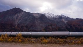 The Trans-Alaska Pipeline Passes in front Of Mountains and Tundra. An oil pipeline carries resources from the far north in Alaska south to refineries stock photography