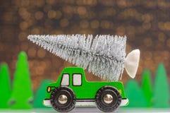 Trans. av en julgran som framläggas med en träbil royaltyfri fotografi