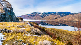 Trans Canada Highway runs along Kamloops Lake with the surrounding mountains reflecting on the quiet surface Stock Image