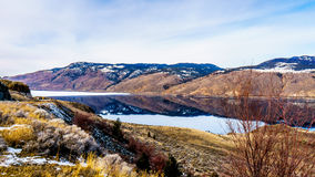 Trans Canada Highway runs along Kamloops Lake with the surrounding mountains reflecting on the quiet surface. Trans Canada Highway runs along Kamloops Lake. The Royalty Free Stock Images