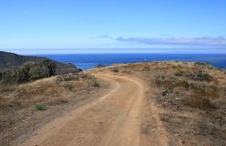 Trans Catalina Trail at Two Harbors. Dirt road heading downhill toward a harbor on a California island Royalty Free Stock Photography
