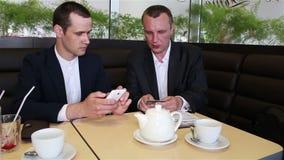 Transação do pagamento de dois biznessmen com a operação bancária em linha video estoque