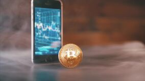 Transação ou investimento de Bitcoins Smartphone com a carta de troca do dinheiro do bitcoin no tela modelo 2018 dourado do bitco video estoque