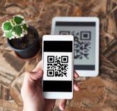 Transacción del pago del código de QR usando los dispositivos móviles del smartphone y de la tableta foto de archivo